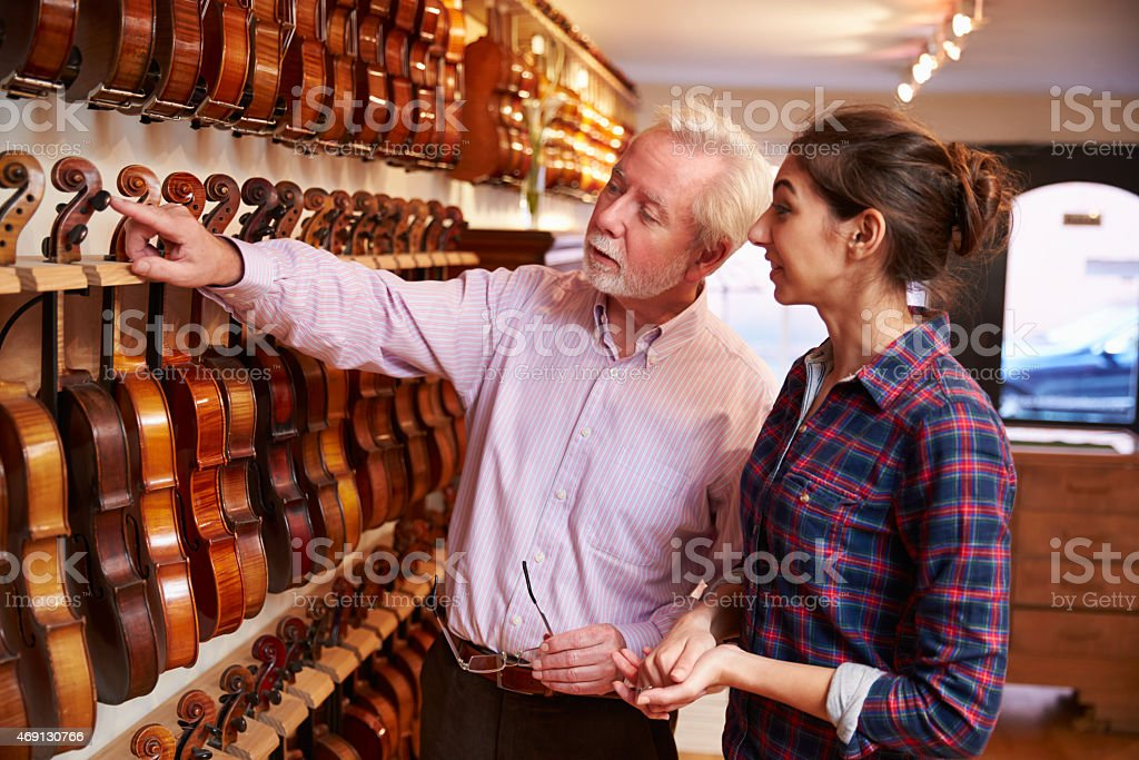 Salesman Advising Customer Buying Violin stock photo