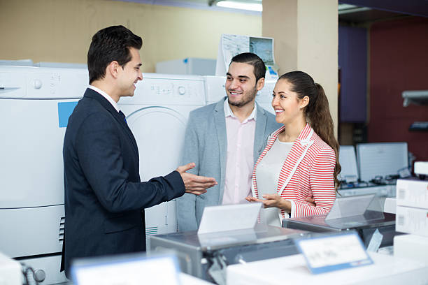 salesman and adult customers in store Positive salesman and adult russian customers in store of domestic appliances armenian ethnicity stock pictures, royalty-free photos & images