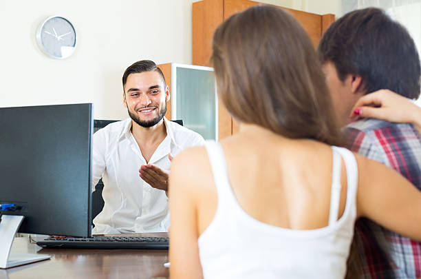 Salesman and couple in the office Smiling salesman telling to young man and woman about the project in the office kantoor stock pictures, royalty-free photos & images