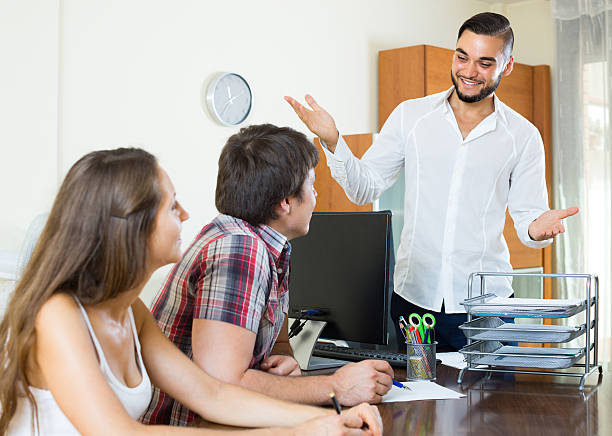 Salesman and couple in the office Cheerful smiling young salesman telling to colleagues about the project in the office kantoor stock pictures, royalty-free photos & images