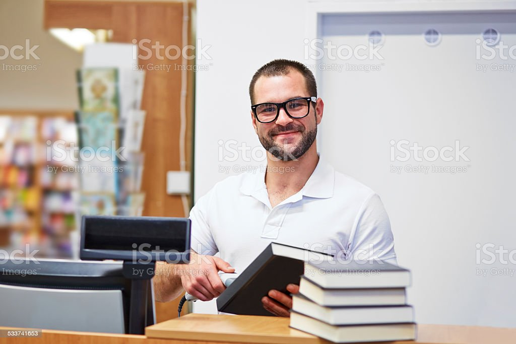 Salesman at the checkout in a bookstore stock photo