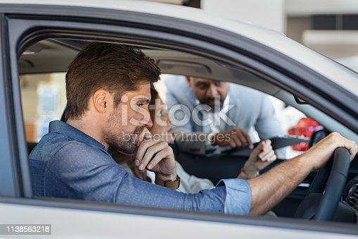 istock Salesman explaining car features 1138563218