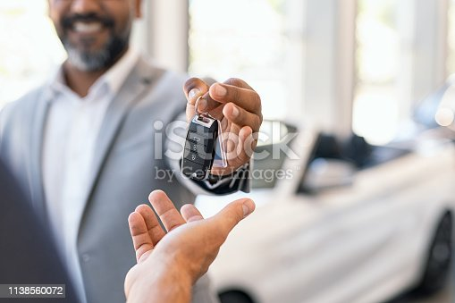 Closeup hand of cardealer giving new car key to customer. Detail of salesman hand giving keys to a client at showroom. Man's hand receiving car keys from african agent in a auto dealership with copy space.