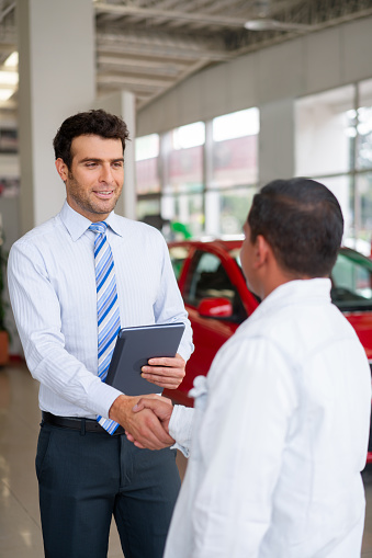 Latin American salesman greeting a client with a handshake at the dealership while showing him cars for sale - business concepts