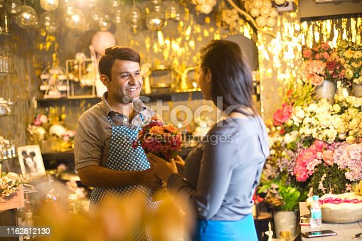 istock Salesman helping woman with choice of flowers 1162812130