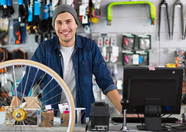 Salesman in bicycle shop Salesman in bicycle shop  bicycle shop stock pictures, royalty-free photos & images