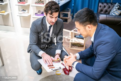 Salesman introducing different materials for shoes.