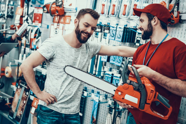 salesman is showing new chainsaw to client - chainsaw stock photos and pictures