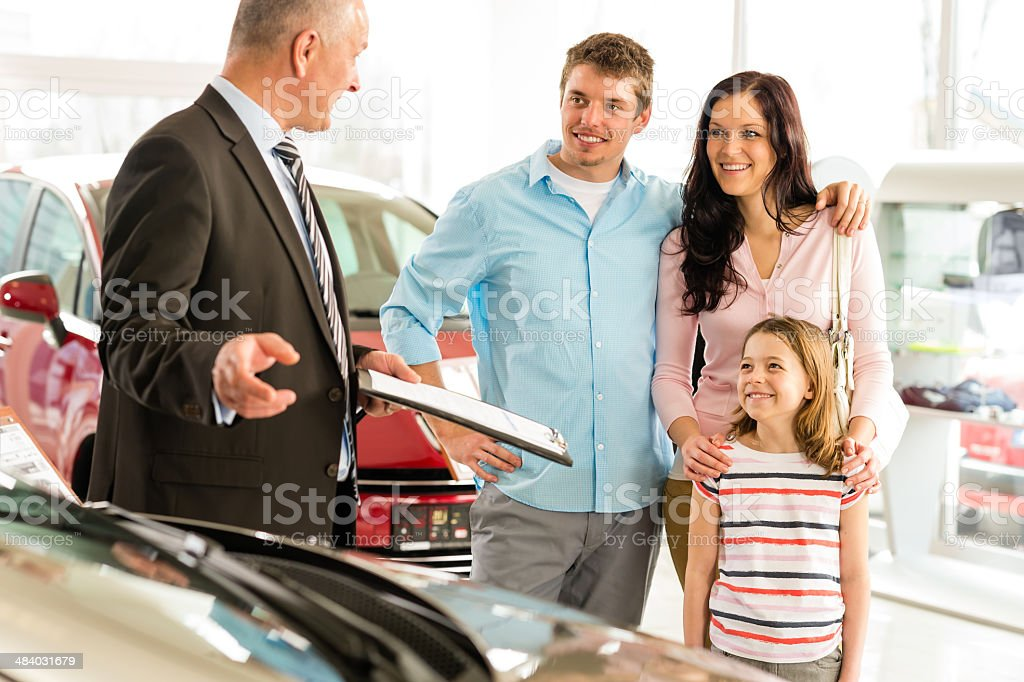 Salesman offering a car to family stock photo