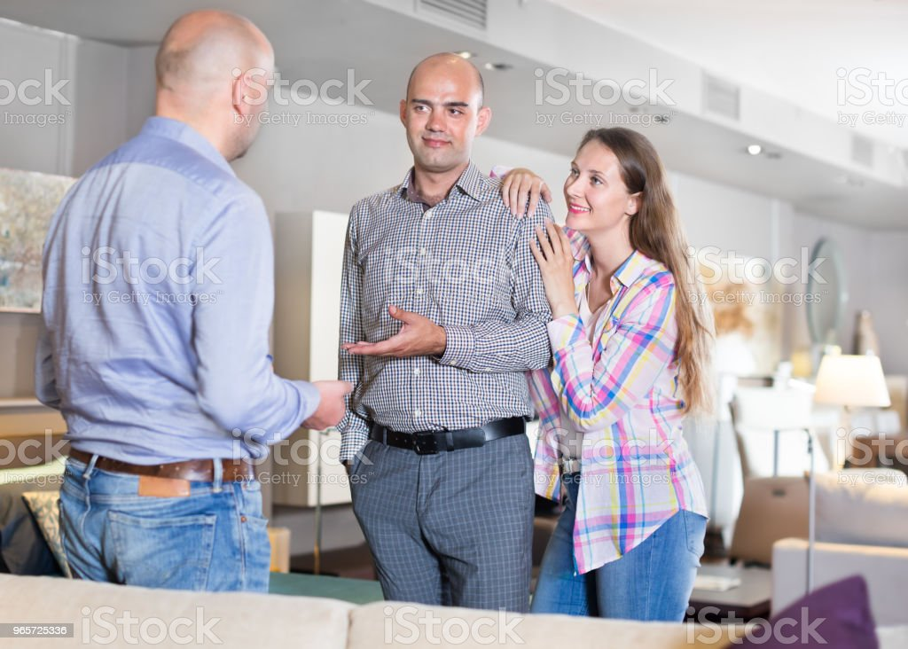 Salesman offering furniture to family couple - Royalty-free Adult Stock Photo