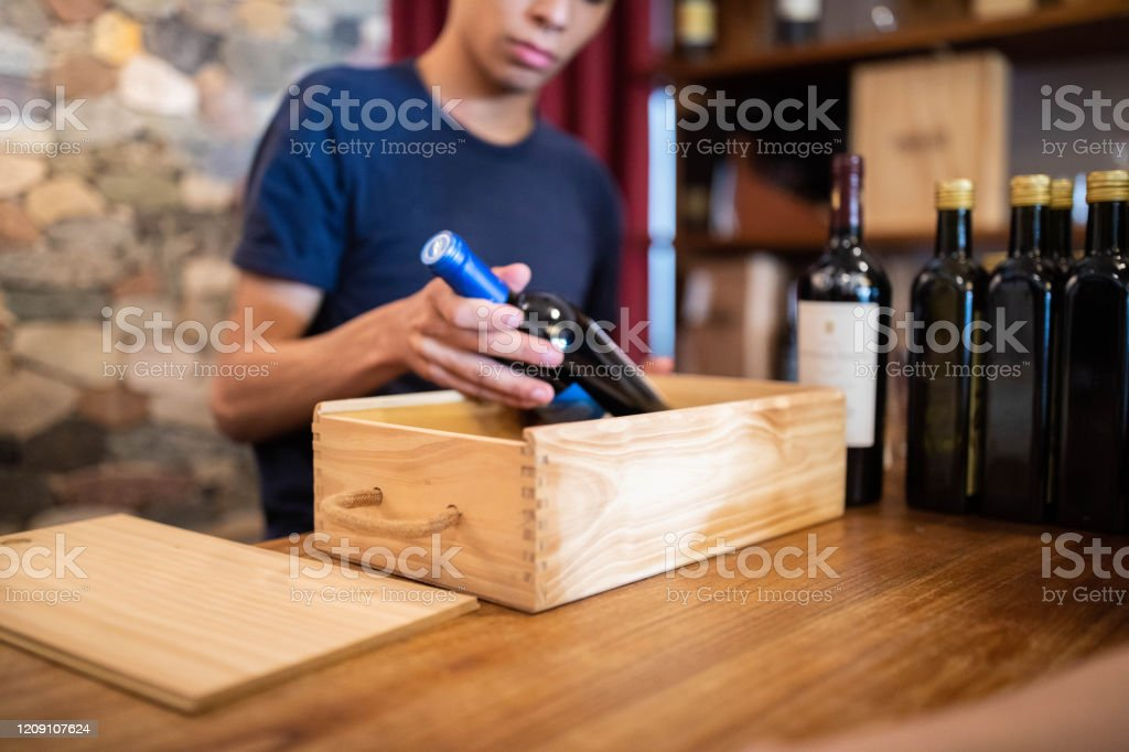 Salesman packing a wine bottle in wooden box - Royalty-free Adult Stock Photo