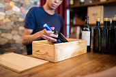 Close-up of man hand packing wine bottle in a wooden box at checkout counter. Salesman packaging a wine bottle for customer at store.