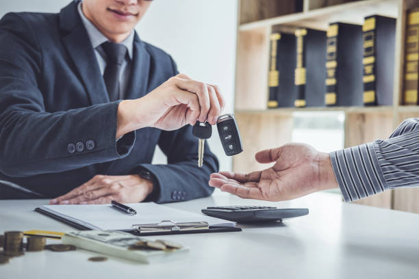 Salesman send key to customer after good deal agreement, successful car loan contract buying or selling new vehicle stock photo