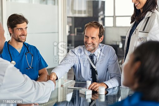 Happy businessman shaking hands with doctor in meeting room. Doctor and representative pharmaceutical shaking hands in medical office. Cheerful salesman with new medicines shaking hands with senior doctor in hospital with medical team sitting at conference table.