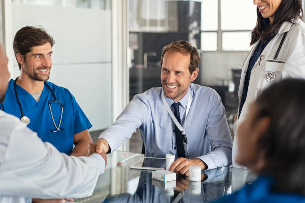 Salesman shaking hands with doctor stock photo