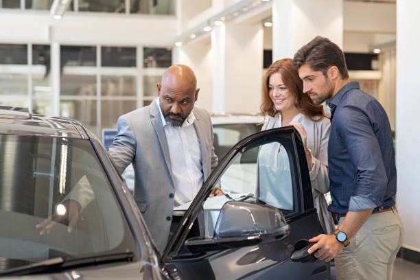 Salesman showing car features to couple Mature african salesman showing all the car features to young couple. Car dealer showing new car to young man and beautiful woman in showroom. Couple buying a new suv in a auto dealership. car salesperson stock pictures, royalty-free photos & images