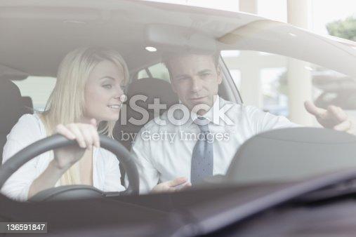 136591825istockphoto Salesman showing car to customer 136591847