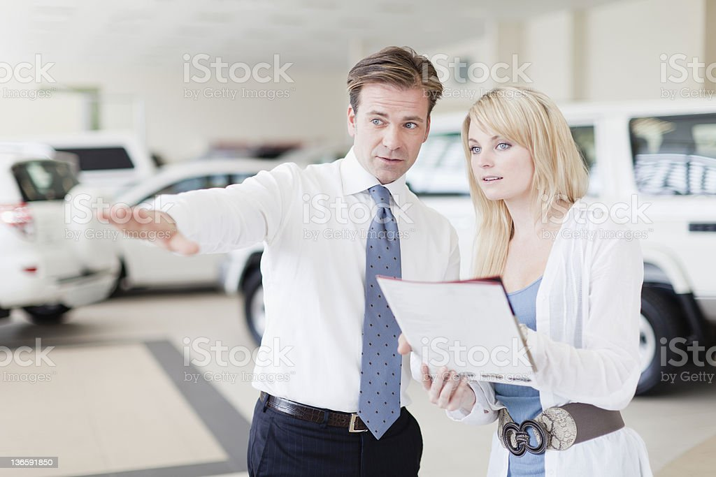 Salesman showing cars to customer royalty-free stock photo