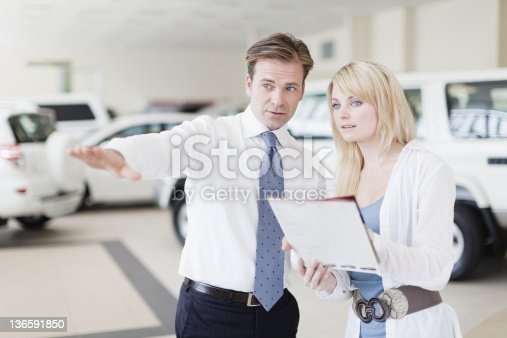 136591850 istock photo Salesman showing cars to customer 136591850