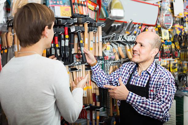 vendedor mostrando diferentes ferramentas - material de construção imagens e fotografias de stock