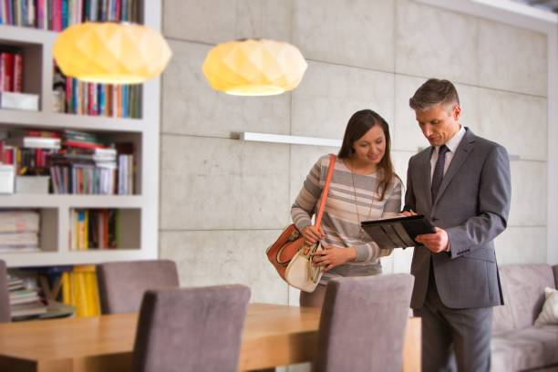 Salesman showing house contract to woman in apartment stock photo