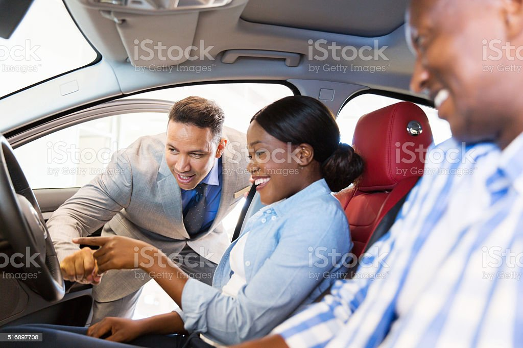 salesman showing new car to african couple stock photo