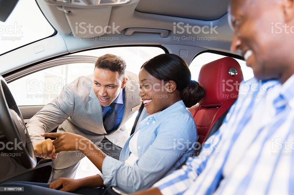 Vendeur montrant nouvelle voiture du couple africain - Photo