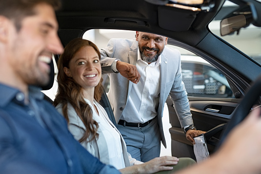 African salesman showing new car to young couple in showroom. Happy man and woman choosing auto in car dealership while cardealer explaining the new technology. Smiling beautiful couple test the comfort of their new suv.