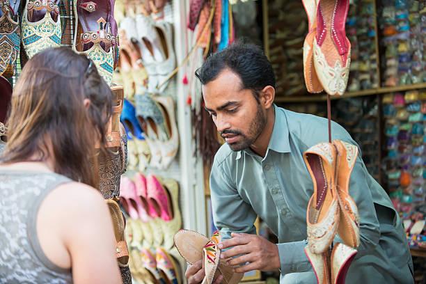 venditore mostrando le scarpe per donna shopping al souk, dubai, emirati arabi uniti - bazar mercato foto e immagini stock