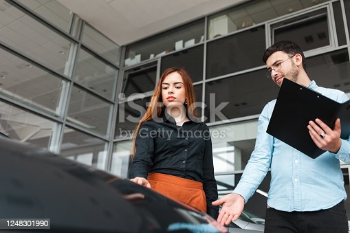 1049198210 istock photo Salesman shows the car to a young client of a car dealership 1248301990