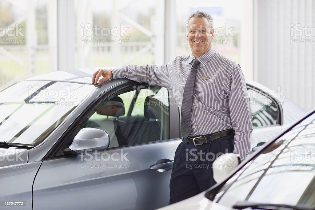 Salesman standing by car in showroom stock photo