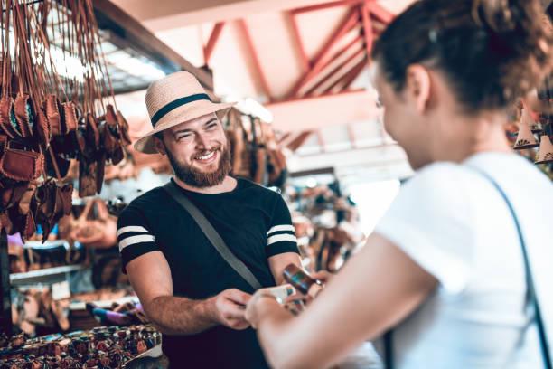 salesman successfully selling leather bag to female tourist - bazar mercato foto e immagini stock