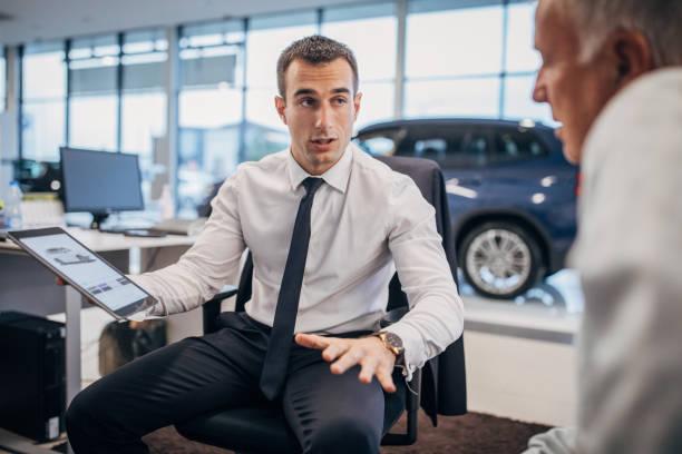 Salesman talking to a senior male customer at the car dealership store stock photo