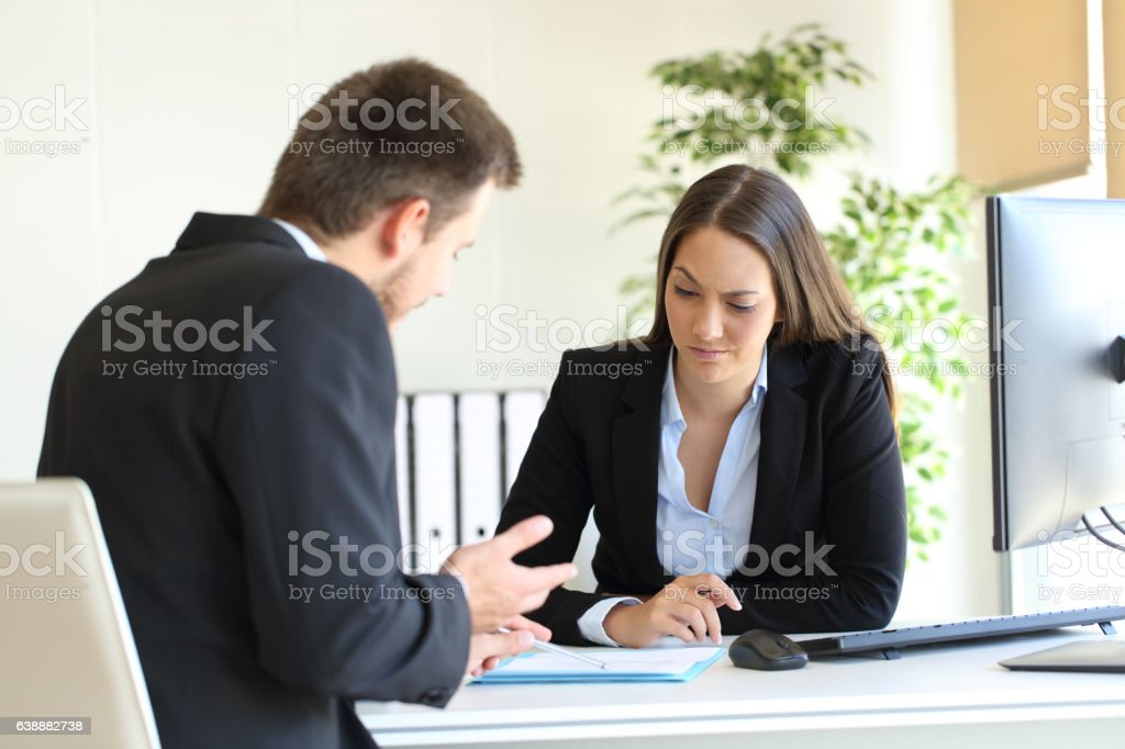 Salesman trying to convince to a doubtful client stock photo