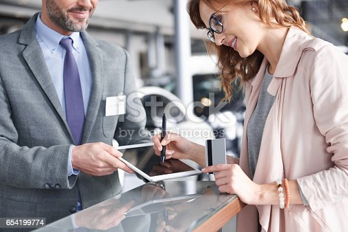 istock Salesman using digital tablet to sign in 654199774