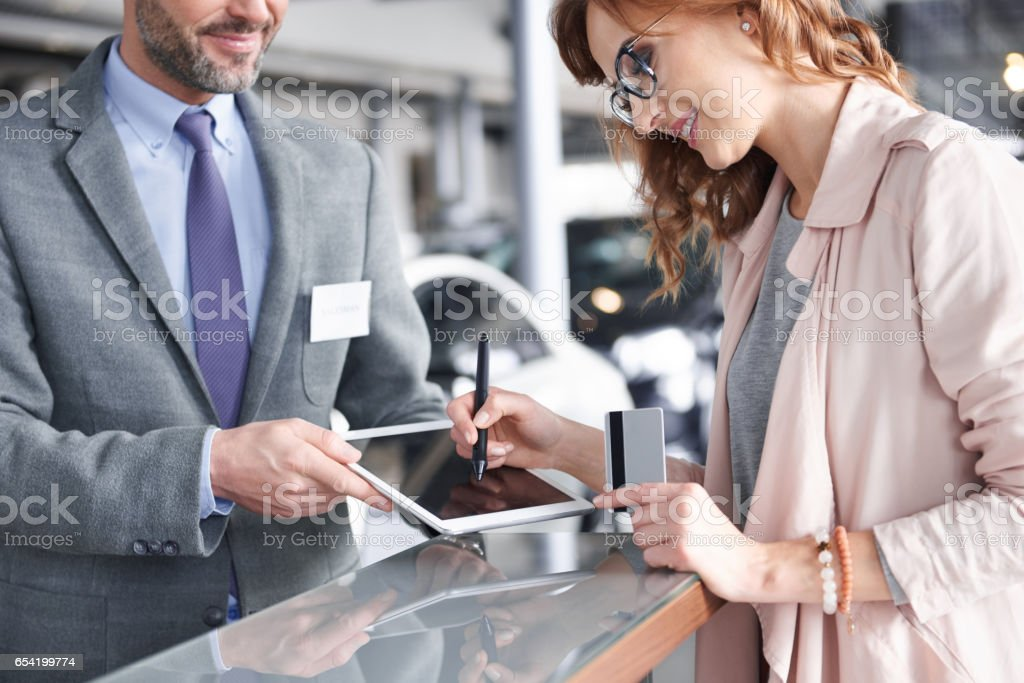 Salesman using digital tablet to sign in stock photo