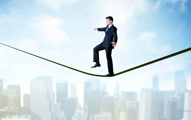 Salesman walking on rope above the city stock photo