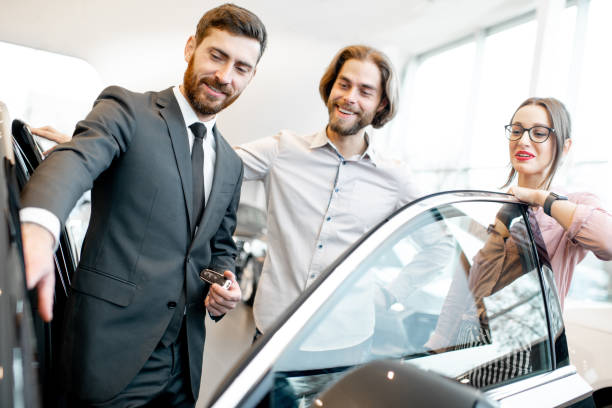 Cтоковое фото Salesman with couple in the car showroom