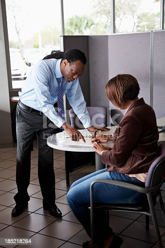 136591825istockphoto Salesman with customer signing contract 185218264