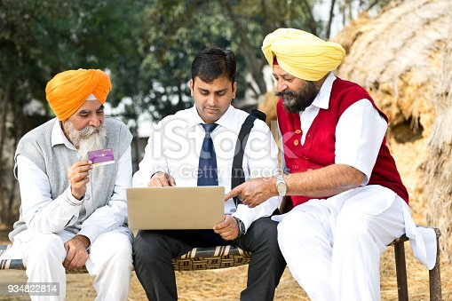 Salesman receiving payment from farmers using laptop and credit card