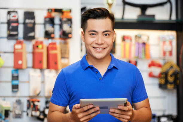 Salesman with tablet pc in the shop Portrait of Asian salesman standing with digital tablet and smiling at camera in workshop salesman stock pictures, royalty-free photos & images