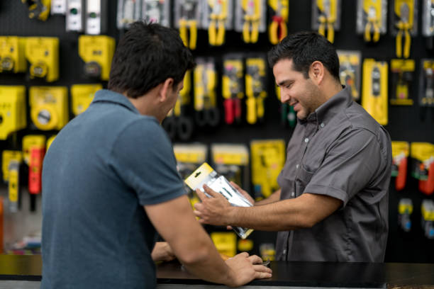 Salesman working at the hardware store and talking to a customer Salesman working at the hardware store and talking to a customer about tools - small business concepts hardware store stock pictures, royalty-free photos & images