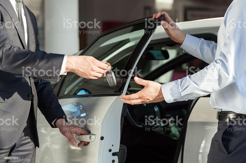 Salesman's hands giving key stock photo