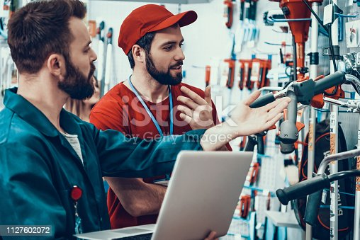 Salesmen is Working in Power Tools Store. Salesmen is Two Bearded Caucasian Men. People is Checking Tools Inventory with Laptop. Men is Wearing Special Uniform. Persons is Talking.