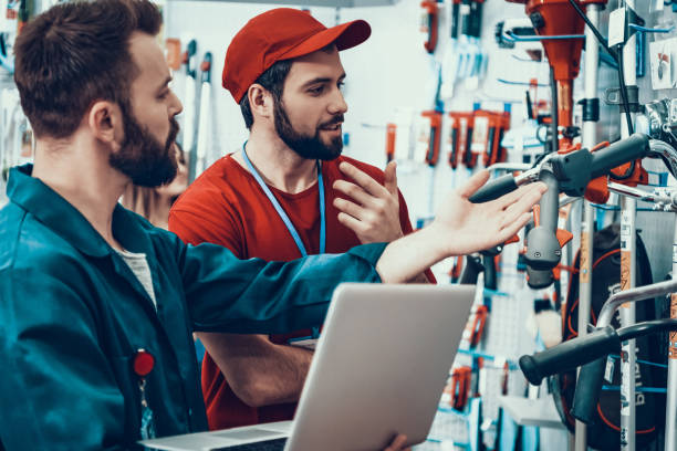 Salesmen is Working in Power Tools Store Salesmen is Working in Power Tools Store. Salesmen is Two Bearded Caucasian Men. People is Checking Tools Inventory with Laptop. Men is Wearing Special Uniform. Persons is Talking. salesman stock pictures, royalty-free photos & images
