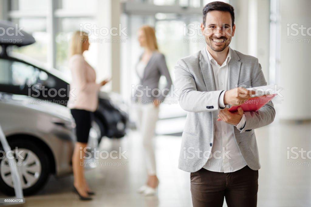 Salesperson at car dealership selling vehichles - foto stock