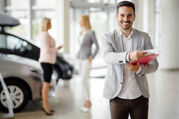 Salesperson at car dealership selling vehichles stock photo