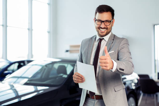 Salesperson at car dealership selling vehicles Salesperson at car dealership selling vehicles car salesperson stock pictures, royalty-free photos & images