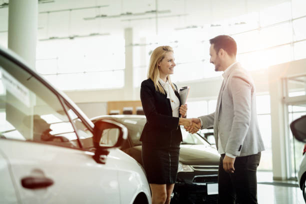 Salesperson selling cars at car dealership Salesperson selling cars at car dealership car salesperson stock pictures, royalty-free photos & images