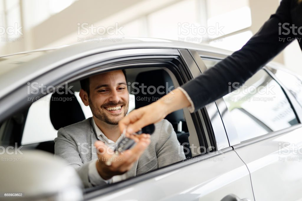 Salesperson selling cars at car dealership stock photo